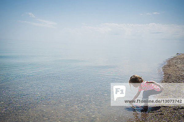 Girl playing in sea at beach against sky