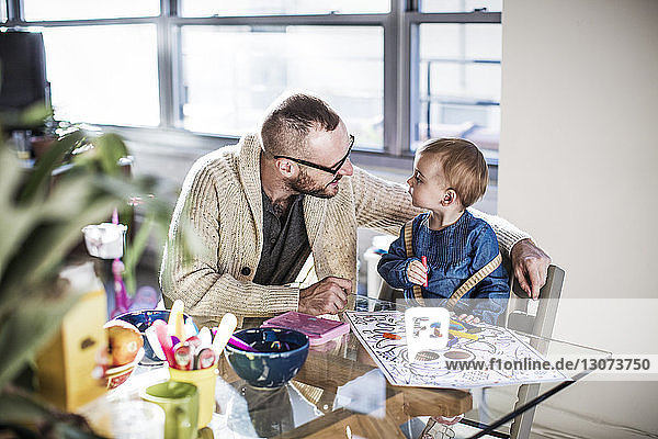 Smiling father drawing with daughter at table in brightly lit living room