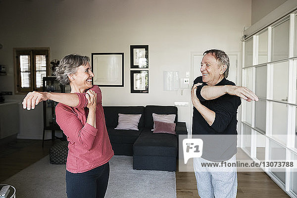Cheerful senior couple exercising at home