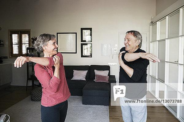Fröhliches älteres Ehepaar trainiert zu Hause