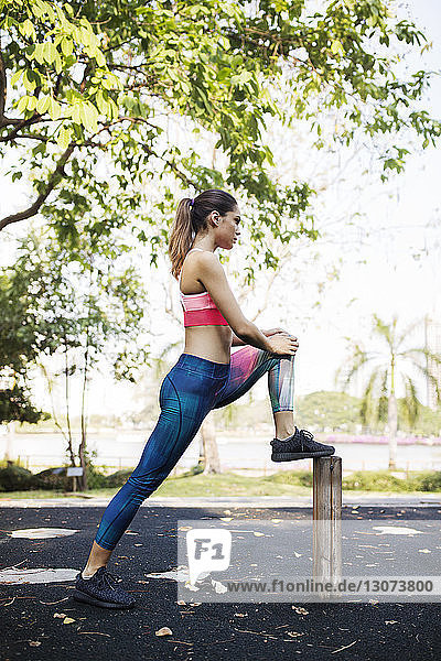Side view of woman stretching while exercising at park