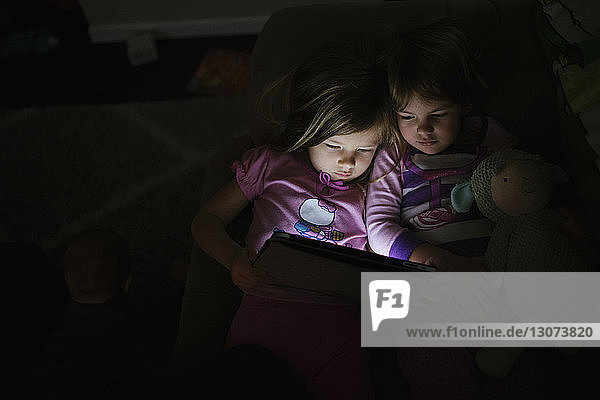 High angle view of sisters holding tablet computer while lying on sofa in darkroom at home