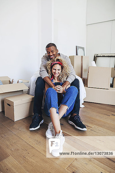 Happy couple using mobile phone while sitting at new home
