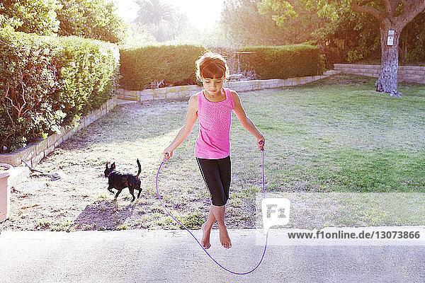 Mädchen springt mit Seil auf dem Feld