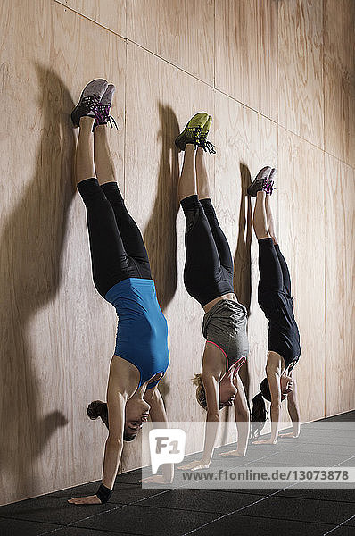 Sportswomen doing handstand exercise by wall in gym