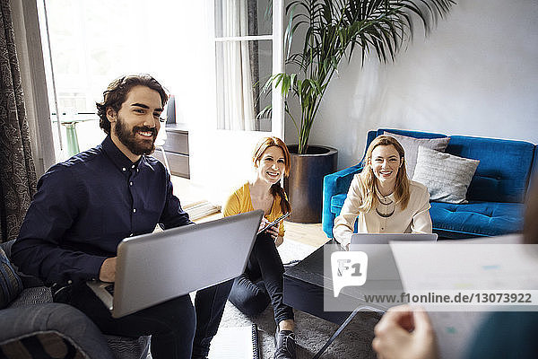 Happy business people looking at colleague during meeting in creative office