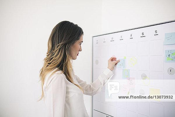 Seitenansicht einer Geschäftsfrau  die im Büro Haftnotizen auf eine Tafel klebt