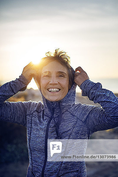 Smiling woman wearing hooded shirt against sky