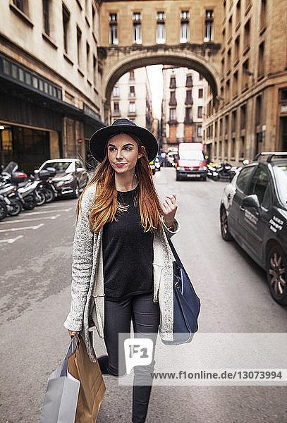 Frau trägt Einkaufstaschen beim Spaziergang auf der Straße in der Stadt