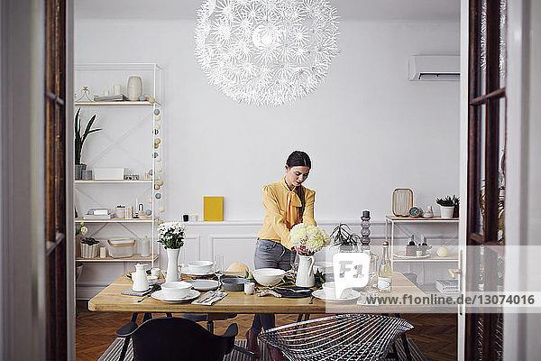 Frau arrangiert Blumen am Esstisch zu Hause