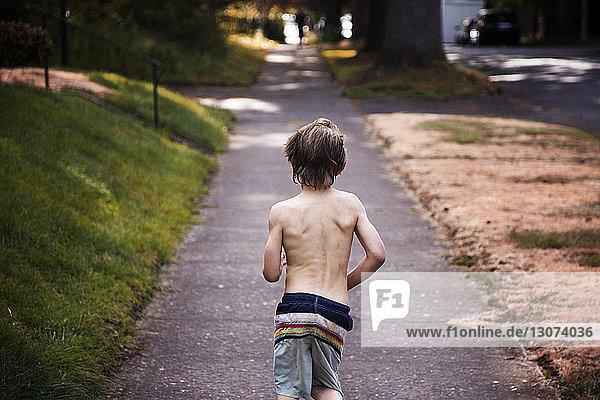 Rear view of shirtless boy running