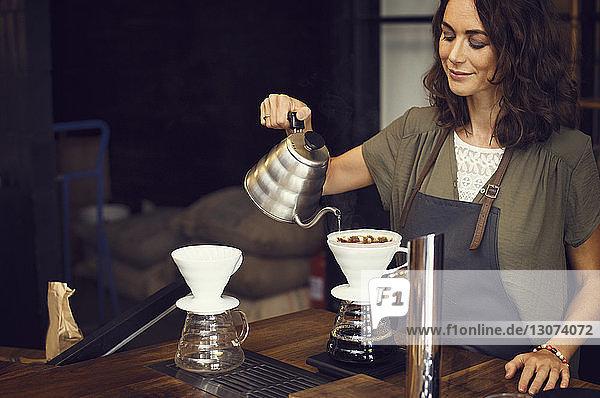Weiblicher Barista bereitet Kaffee im Café zu