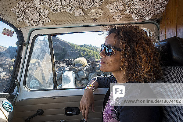 Thoughtful woman looking away while wearing sunglasses in camper trailer