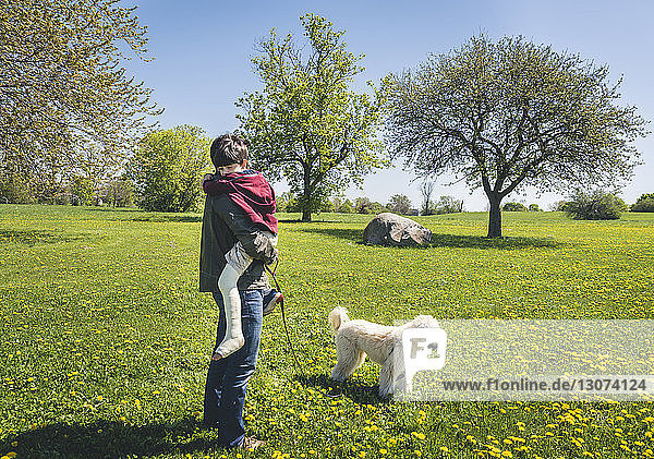 Side view of father carrying son with broken leg while standing by dog on grassy field at park