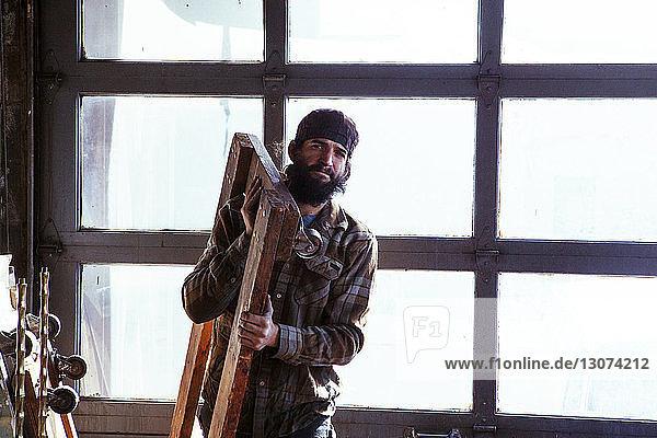 Portrait of worker carrying wooden equipment in workshop