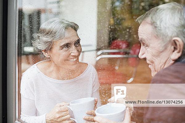 Glückliches älteres Ehepaar unterhält sich  während es Kaffeetassen in der Hand hält  die durch ein Glasfenster gesehen werden