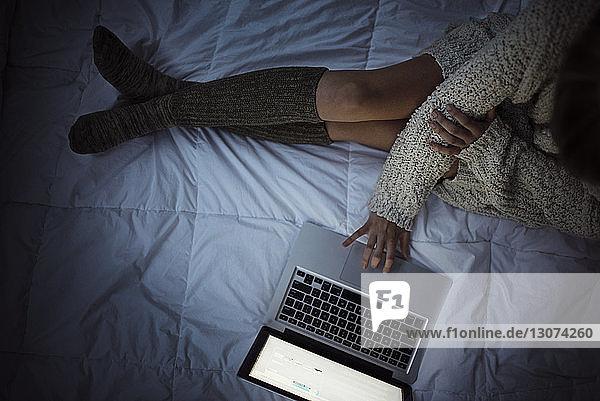 Niedriger Teil der Frau  die einen Laptop benutzt  während sie auf dem Bett sitzt