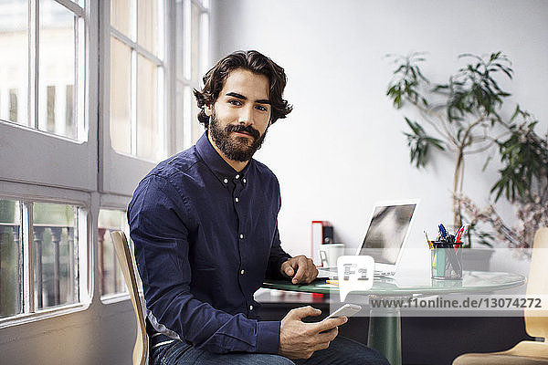 Portrait of confident businessman holding smart phone while sitting in office
