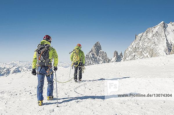 Rückansicht von Wanderern mit Seil  die auf einem schneebedeckten Berg bei strahlend blauem Himmel gehen