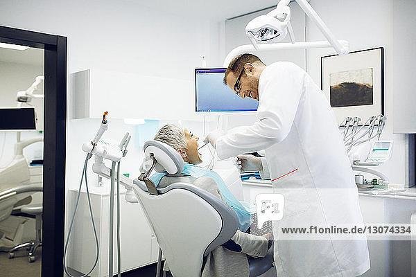 Dentist examining patient's teeth at clinic