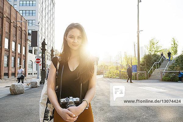Porträt einer jungen Frau mit Kamera auf der Straße in der Stadt vor klarem Himmel
