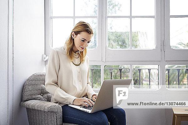 Lächelnde Geschäftsfrau benutzt Laptop  während sie im Büro auf einem Stuhl sitzt