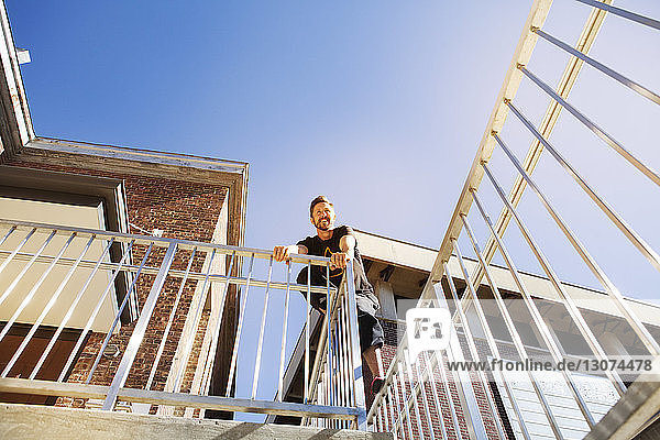 Low angle view of smiling man standing on building railing against clear blue sky