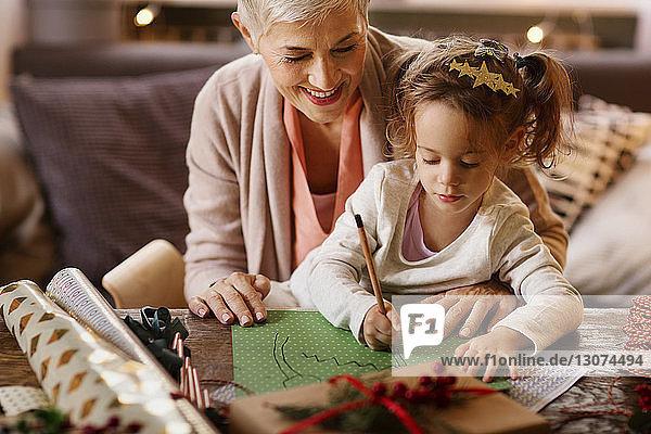 Großmutter und Enkelin zeichnen bei Tisch auf Papier