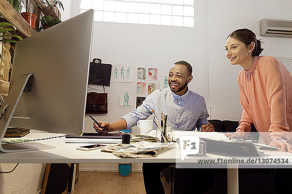 Happy male illustrator discussing with colleague at desk in creative office