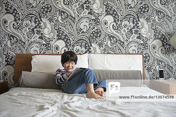 Smiling boy using digital tablet while sitting on bed