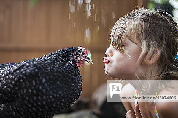 Happy girl puckering hen outdoors