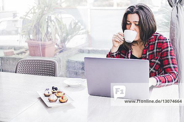 Frau trinkt Kaffee  während sie ihren Laptop auf dem Tisch im Café benutzt