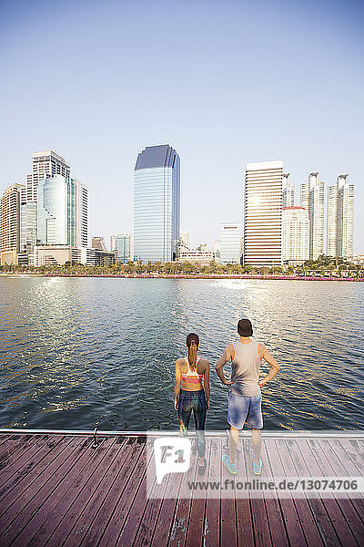 Rear view of couple standing on wooden walkway by river against cityscape