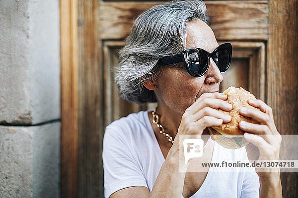 Frau mit Sonnenbrille isst Burger  während sie an der Tür sitzt