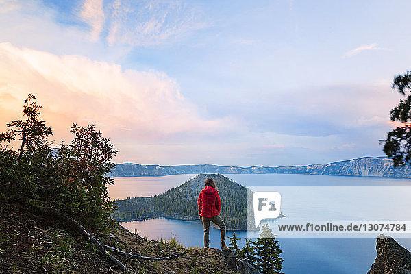 Rückansicht einer Frau  die auf einer Klippe vor dem Kratersee steht