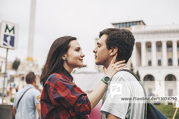 Side view of young couple looking each other face to face in city