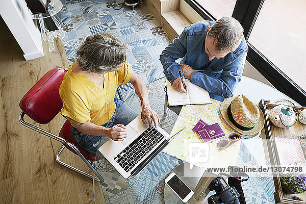 Overhead view of senior couple planning vacation at home
