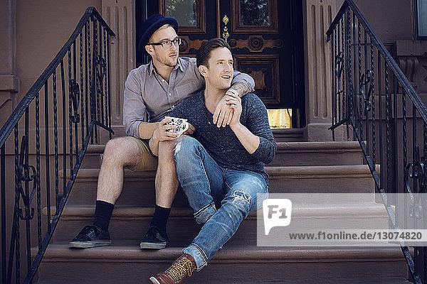 Schwules Paar sitzt auf Stufen gegen Gebäude