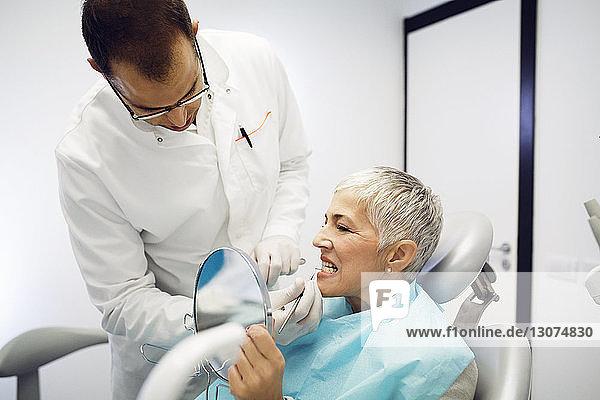 Dentist checking woman's teeth at clinic