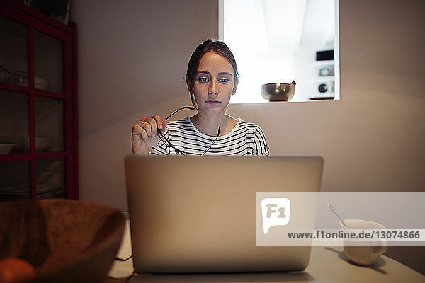 Woman holding eyeglasses while using laptop at table