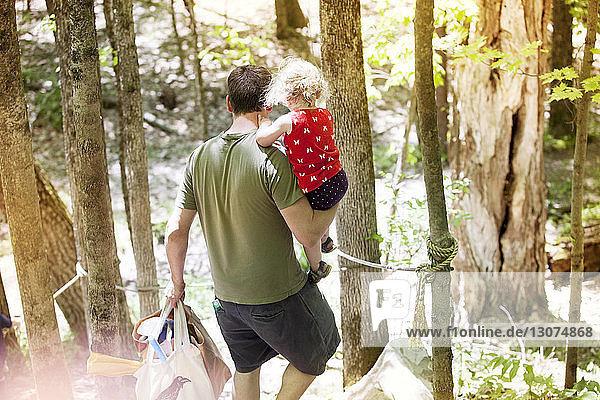 Hochwinkelaufnahme eines Vaters  der seine Tochter und Taschen trägt  während er im Wald spazieren geht