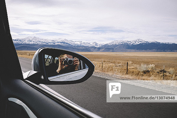Reflection of woman photographing seen in side-view mirror against mountains and cloudy sky