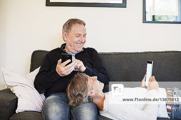 Happy senior couple using tablet computer on sofa