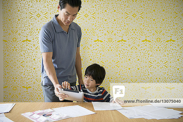 Father assisting boy with homework through tablet at home