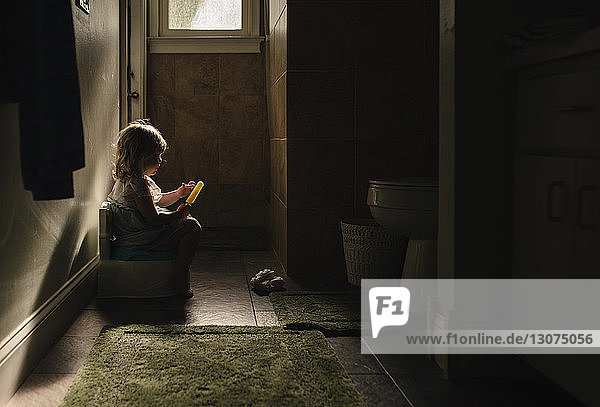 Side view of baby girl on potty while holding popsicle in darkroom at home