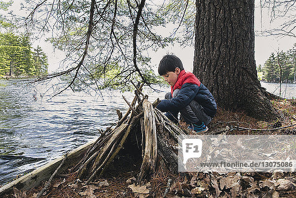 Full length of boy crouching by firewood on lakeshore in forest