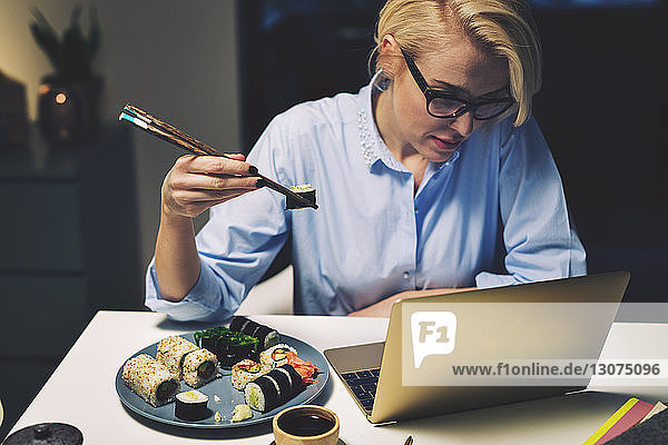 Businesswoman looking having food while working at desk in home office
