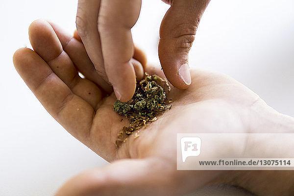 Geschnittene Hände eines Mannes  der Marihuana-Joints und Tabakwaren mischt
