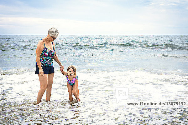 Playful girl with grandmother standing in water on shore at beach