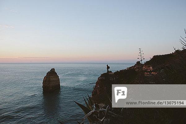 Mitteldistanzansicht des auf einer Klippe am Meer stehenden Silhouettenmannes gegen den Himmel bei Sonnenuntergang